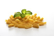 close up with macaroni and basil on white background