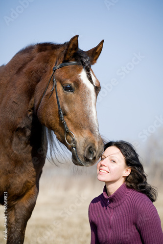 Young girl and bay horse at spring