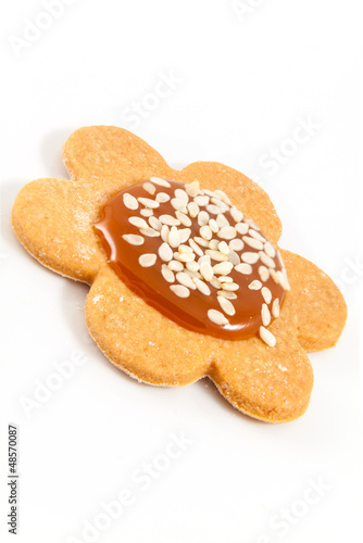Single homemade cookie with caramel and sesame seeds on white ba