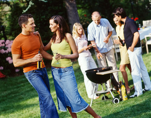 Junge Leute grillen bei einer Gartenparty