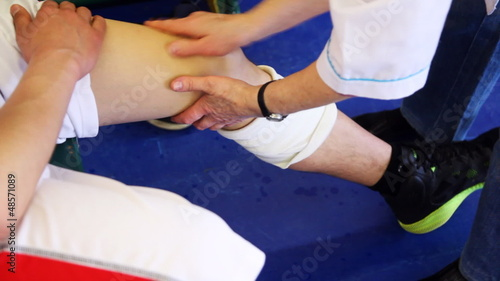 sports doctor does massage patella of sportsman