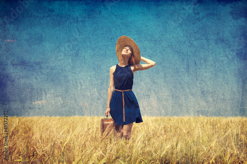 Lonely girl with suitcase at country. Photo in old color image s