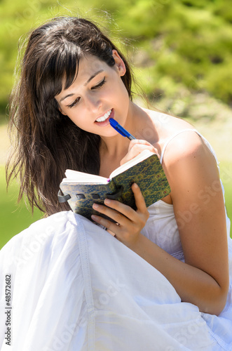Pretty girl reading and writing in her diary