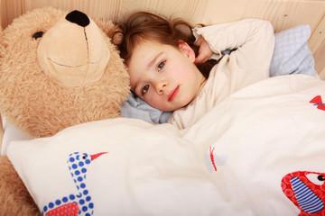 Ein kleines Mädchen liegt in seinem Bett