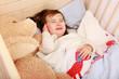 Leinwanddruck Bild - Ein kleines Mädchen liegt in seinem Bett und weint