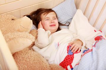 Ein kleines Mädchen liegt in seinem Bett und weint