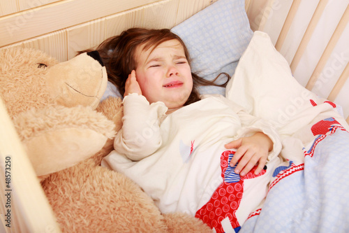 Ein kleines Mädchen liegt in seinem Bett und weint - 48573250