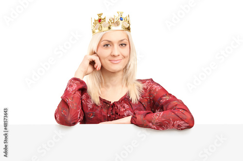 Beautiful queen with a diamond crown posing behind panel