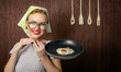 Happy funny woman cook holding pan with fried egg