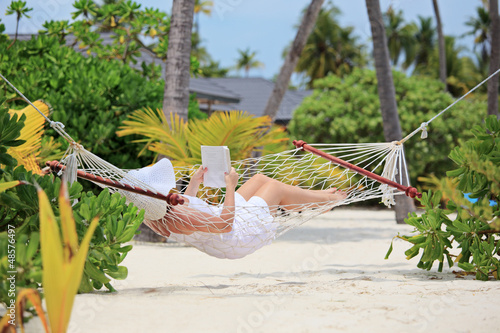 Woman relaxing in a hammock and reading a book on a beach
