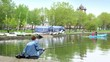 Fisherman on pond in city park, family sail on boat