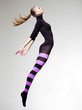 woman with perfect body jumping dressed in purple striped tights