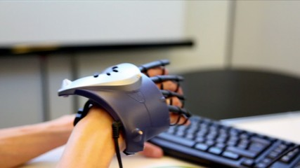 Hand with virtual manipulator moves at background of keyboard