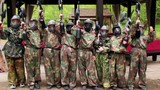 Eight teenagers paintball team stand and aim weapon