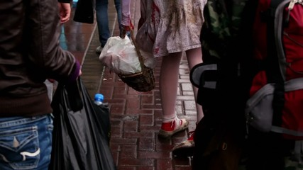 Girl in bloody dress walks by pavement with basket