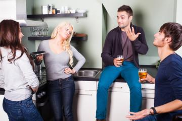 4 Freunde in der Küche beim gemeinsamen kochen