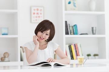 部屋で雑誌を読む若い女性