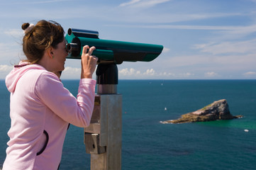 Woman to look through binoculars, island