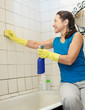 woman cleans tile with sponge in bathroom