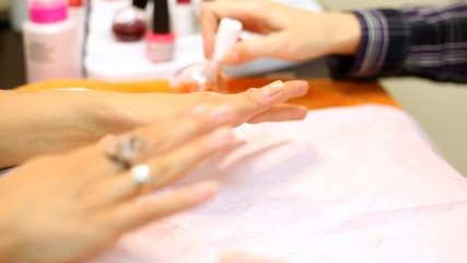 Cosmetician colors nails of woman