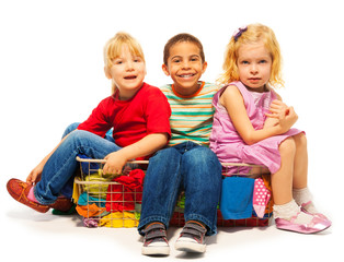 three kids sitting in the clothes basket