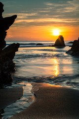 Sunset over beach, waves and ocean with stunning reflections.
