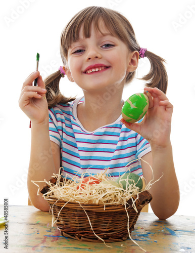 a happy little girl painting easter eggs