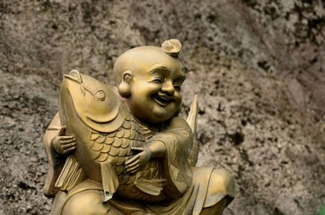 Golden, laughing Buddhist monk with fish of good fortune