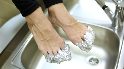 Woman fingers wrap up in foil to make correction of nails above