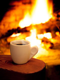 A cup of hot coffee in front of fireplace