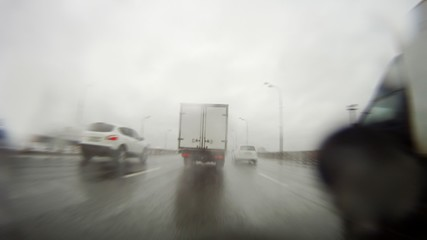 Cars go on wide range highway during rain