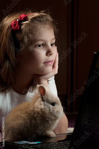 girl with a small bunny looking and laptop