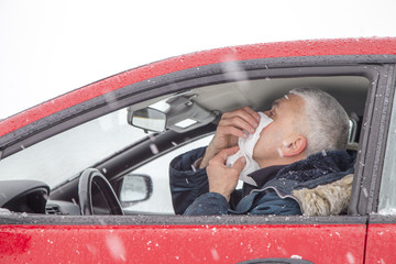 Mid aged man with flu symptoms sneezes in a car on snowy day