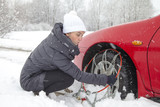 Young woman driver mounting car tyre chains on snowy winter road