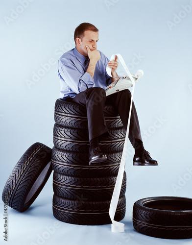 Mann sitzt auf Reifenstapel