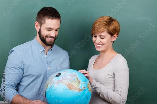 zwei studenten schauen auf globus