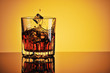 Glass of whisky with ice against yellow background