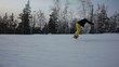 STEADYCAM: Snowboarder riding down the hill. Follow shot.
