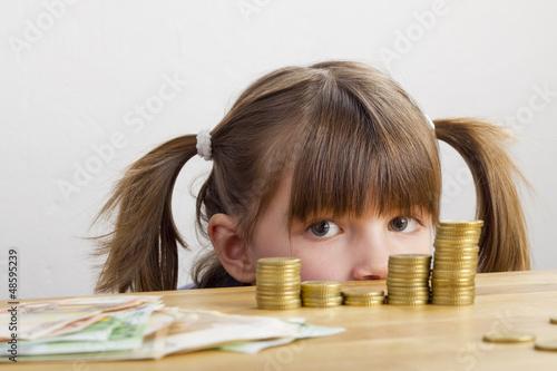 Mädchen schaut auf Geldtürme - 48595239