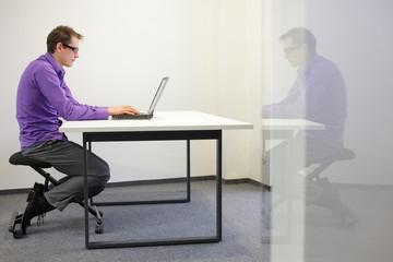 bad sitting posture  at workstation. man on kneeling chair