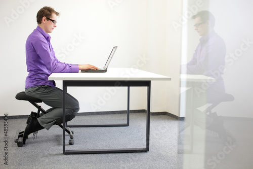 correct sitting position at workstation. man on kneeling chair