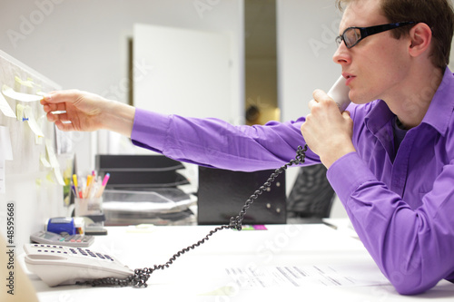 young business man on phone reading note in office