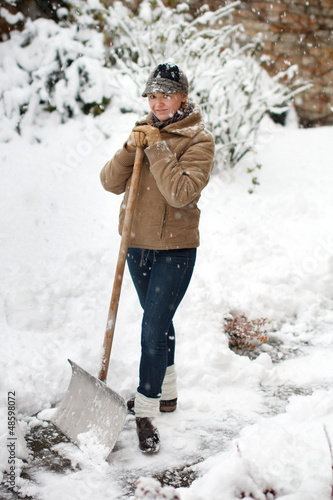 Woman posing with snow shovel