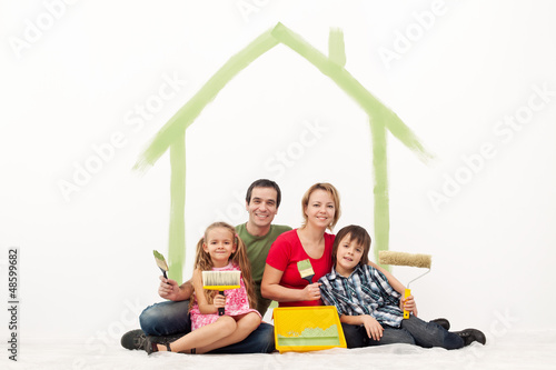 Happy couple with two kids repainting their home