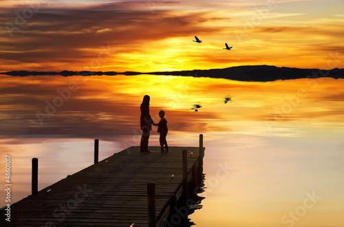 Deurstickers Pier madre e hijo disfrutando de la puesta de sol