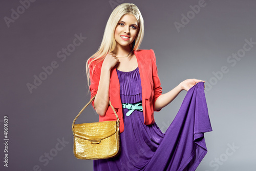 attractive blonde girl with leather handbag and purple dress