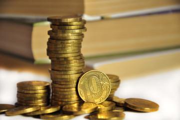 столбики монет на фоне книг