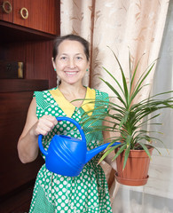 woman watering pot with dracaena