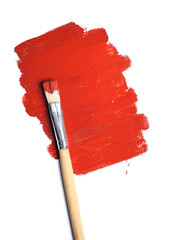 Image of paintbrush and red paint spot isolated