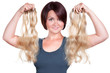 Frau hält Haarverlängerungen in  die Kamera